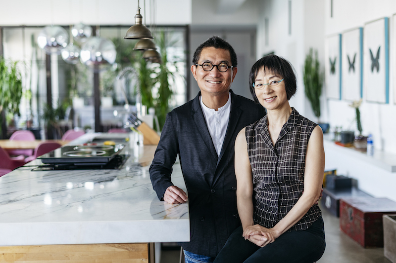 Stylish Chinese couple in modern office smiling towards camera